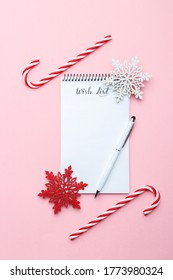 Christmas or new year wish list, pen and wooden ornaments on pink background, festive decorations, vertical