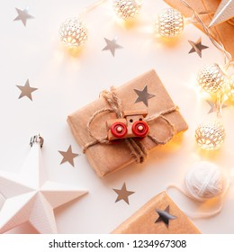 Christmas and New Year wrapped DIY presents in craft paper. Gift tied with rustic thread with toy train as decoration. Metal light bulbs with delicate pattern. Christmas tree decorations.