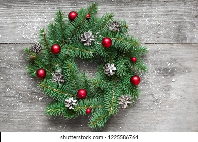 Christmas or new year wreath with red decorations and pine cones on rustic wooden table covered with snow. top view. flat lay