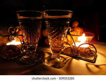 Christmas and New Year`s bokeh image. Two vintage champagne wineglass festive evening candle and gentle sweet green grapes. Greeting card Background holiday concept  for restaurant or coffee party.