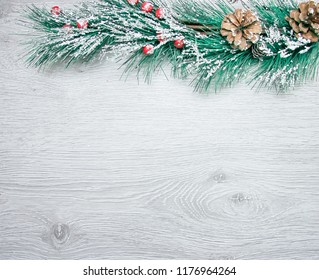 Christmas and New Year's composition. The pine cones, spruce branches on a wooden white background, top view