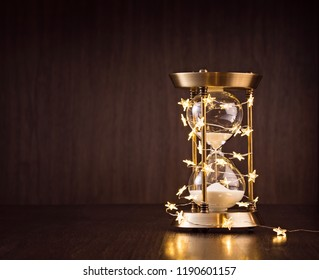 Christmas or new years countdown. Hourglass wrapped in lights on a wooden background.