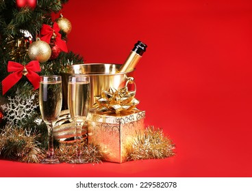 Christmas or New Year's Eve. Champagne and Presents over Red Background. Celebration
