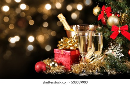 Christmas or New Year's Eve. Champagne and Presents over Black Background