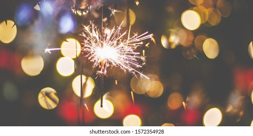 christmas and new years eve themes background with sparklers and christmas tree in background