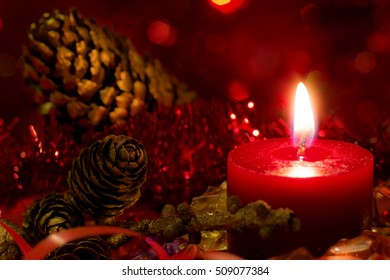 Christmas and New Year`s festive evening burning candle bokeh image. Greeting card dark Background concept with holiday tinsel, fir cones, tree banch and copyspace place for text or logo.