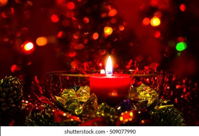 Christmas and New Year`s festive evening burning candle bokeh image. Greeting card  red lights Background concept with holiday colorful glass tinsel, and copyspace place for text or logo.
