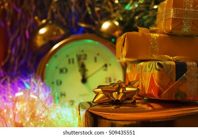 Christmas and New Year`s many gift boxes wrapped in colorful and gold wrapping paper with bows of ribbons. Retro vintage clock at five of midnight. Greeting card blue Background with holiday tinsel.