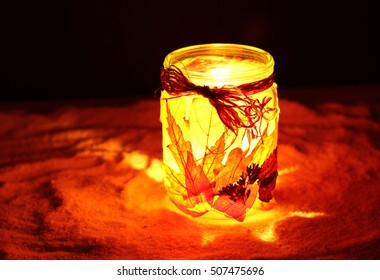 Christmas an New Years street lamp on snow  in night with candle. Hand made from autumn leaves