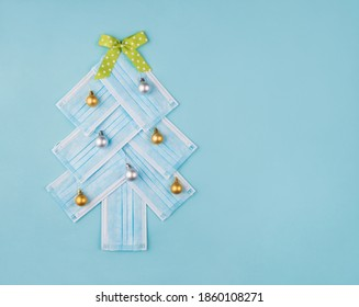 Christmas and newyear celebration concept. Photo of tree made of disposable mask decorated with toy balls and green dotted bow isolated pastel color background