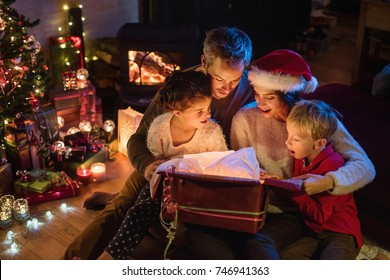 Christmas night. A family opens its gifts, children and parents are very happy to discover a digital tablet in a gift box.