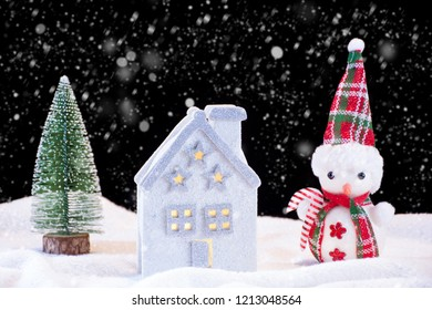 Christmas night idyll with small house toy and snowman and fir tree. It's snowing and snowflakes falling down. Winter and holiday concept image