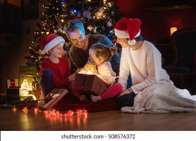 Christmas night. Near the christmas tree a lovely family opening their gifts. They enjoy the warm Christmas atmosphere in their living room, mom and kids wearing a hat of Santa Claus.