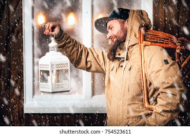 Christmas night, snow falling, funny man with a beard and with gifts in hand and flashlight at the window. Winter background