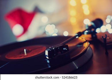 Christmas, Noel. Turntable vinyl record player. Sound technology for DJ to mix & play music. Vintage vinyl record player on a background of Christmas decorations, cap, wreath and lights