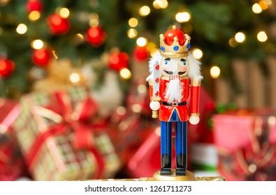 Christmas nutcracker figurine. Christmas tree and presents, bokeh background.