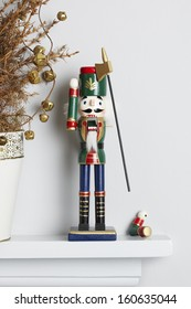 Christmas nutcracker solider broken on mantle piece with decorated dead pine tree. Unhappy xmas concept
