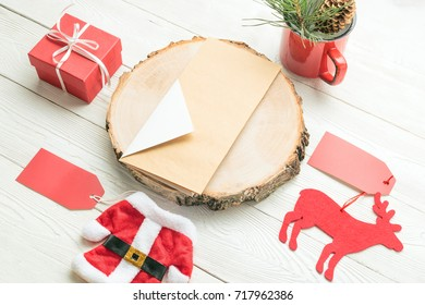Christmas objects including paper card, Santa toy costume, deer toy, mug with fir decor, gift box on white background