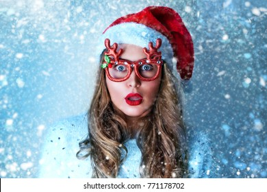 Christmas, office or birthday concept. Surprised Woman in Santa Claus hat and funny glasses. Happy smiling and exciting looking at camera funny hipster beautiful young lady