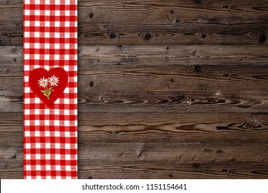 Christmas or oktoberfest background with red heart with White  Edelweiss  on fabric checkered tablecloth. Table  Runner on wooden table rustic background. Copy space for text, mock up