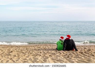 Christmas on a beach. Couple wearing Santa hats looking out to the sea.