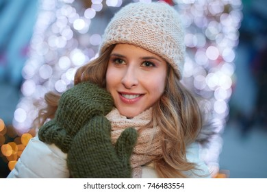 Christmas on the street. Young happy woman outdoor during christmas time in front of christmas lights.