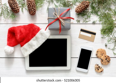 Christmas online shopping background. Mobile and tablet screen with copy space top view on white wood, credit card, present boxes and santa hat. Internet commerce on winter holidays concept