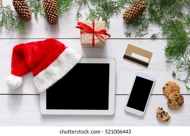 Christmas online shopping background. Mobile and tablet screen with copy space top view on white wood, credit card and santa hat. Internet commerce on winter holidays concept