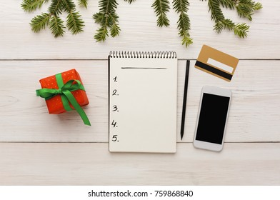 Christmas online shopping. Smartphone, credit card, gift box in red paper with green ribbon, shopping list with copy space on white wooden table. Winter holiday concept. Top view
