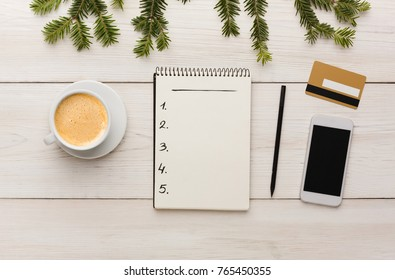Christmas online shopping. Smartphone, credit card, cup of coffee, shopping list with copy space on white wooden table. Winter holiday concept. Top view