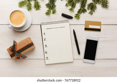 Christmas online shopping. Smartphone, credit card, gift box in beige paper with ribbon, cup of coffee and shopping list with copy space on white wooden table. Winter holiday concept. Top view