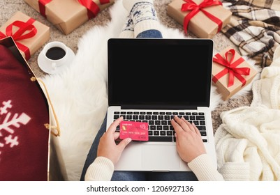 Christmas online shopping. Woman buying presents for xmas on laptop with credit card, copy space on screen