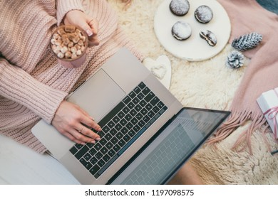 Christmas online shopping. Woman buys presents, prepare to xmas eve. Female with laptop, copy space on screen. Hot coffee, spice and almond cakes on tray. Cozy blanket. Toned image. Soft focus.