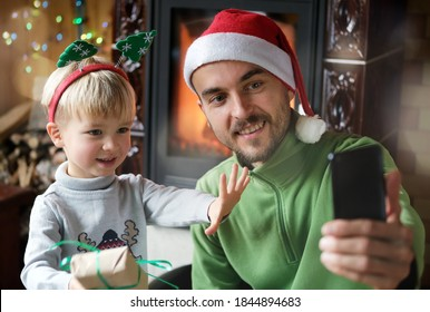 Christmas online video chatting, online greetings. Cheerful father and son using smartphone for virtual call and congratulations family and friends or making selfie photo. New year home celebration.