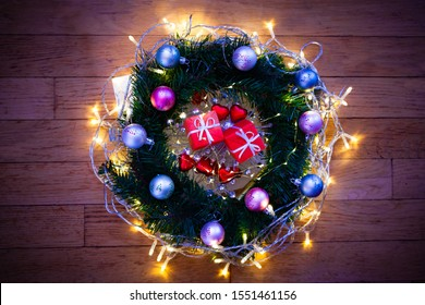 Christmas ornament and background. Very bright and tinsel, gifts in red wrappers and green spruce. Wooden floor background. Flat lay view. closeup.