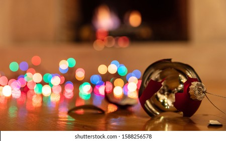 Christmas ornament broken. Xmas holiday decoration, lights glowing, blur burning fireplace background, reflections on the wood floor
