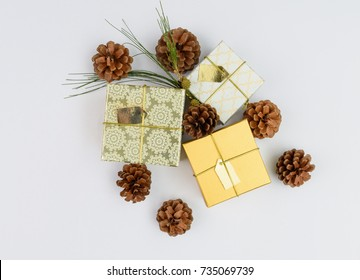 Christmas ornament golden gift boxes set and pine cones fresh green branch on white background,flat lay