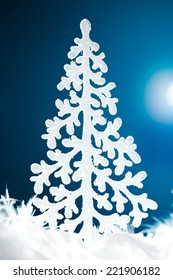 Christmas ornament shaped as a Christmas tree against blue background.