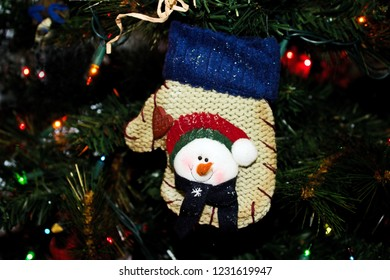 Christmas Ornament of a Snowman on a Wool Mitten hanging on an evergreen tree