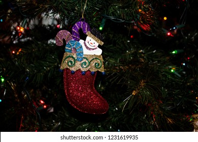 Christmas Ornament of a Snowman in a Stocking hanging on an evergreen tree