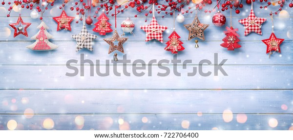 Christmas Ornaments And Berries Hanging On Snowy Wooden