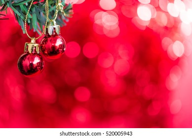 Christmas ornaments decoration hanging on fir tree branches over red bokeh night light background with copy space, greeting card happy new year 2017