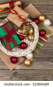 Christmas ornaments, gifts and wrapping paper on a gray wooden background.