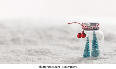 Christmas ornaments of glass jar with striped ribbon , bells and fir trees inside on snow background