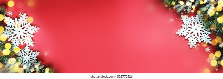 Christmas ornaments on red background, border design, top view