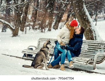 Christmas outdoor full-length portrait of the happy couple kissing on the bench during their walk with siberian husky in the snowy forest.