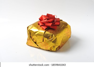 christmas panettone cake isolated on white background in its own gold-colored packaging