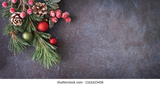 Christmas panoramic background with pine twigs, cones and berries on dark background, text space