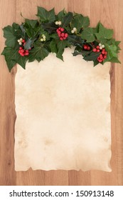 Christmas parchment blank letter with border of holly, ivy and mistletoe over oak background.