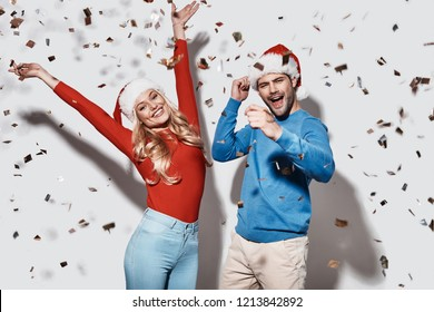 Christmas party. Beautiful young couple in Christmas hats gesturing and smiling while standing against grey background